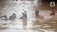 Anak-anak berenang di salah satu gang di Kawasan Rawajati yang tergenang banjir, Jakarta, Rabu Rabu (1/1/2020). Hujan yang mengguyur Jakarta sejak Selasa sore (31/12/2019) mengakibatkan banjir di sejumlah titik di Jakarta. (Liputan6.com/Helmi Fithriansyah)