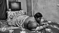 Ariya sedang bemain game dengan gadget kesayangannya di kamarnya. Hiburan bisa membuatnya senang ditambah dengan isi metode pembelajaran sekolah. (Liputan6.com/Gempur M Surya)