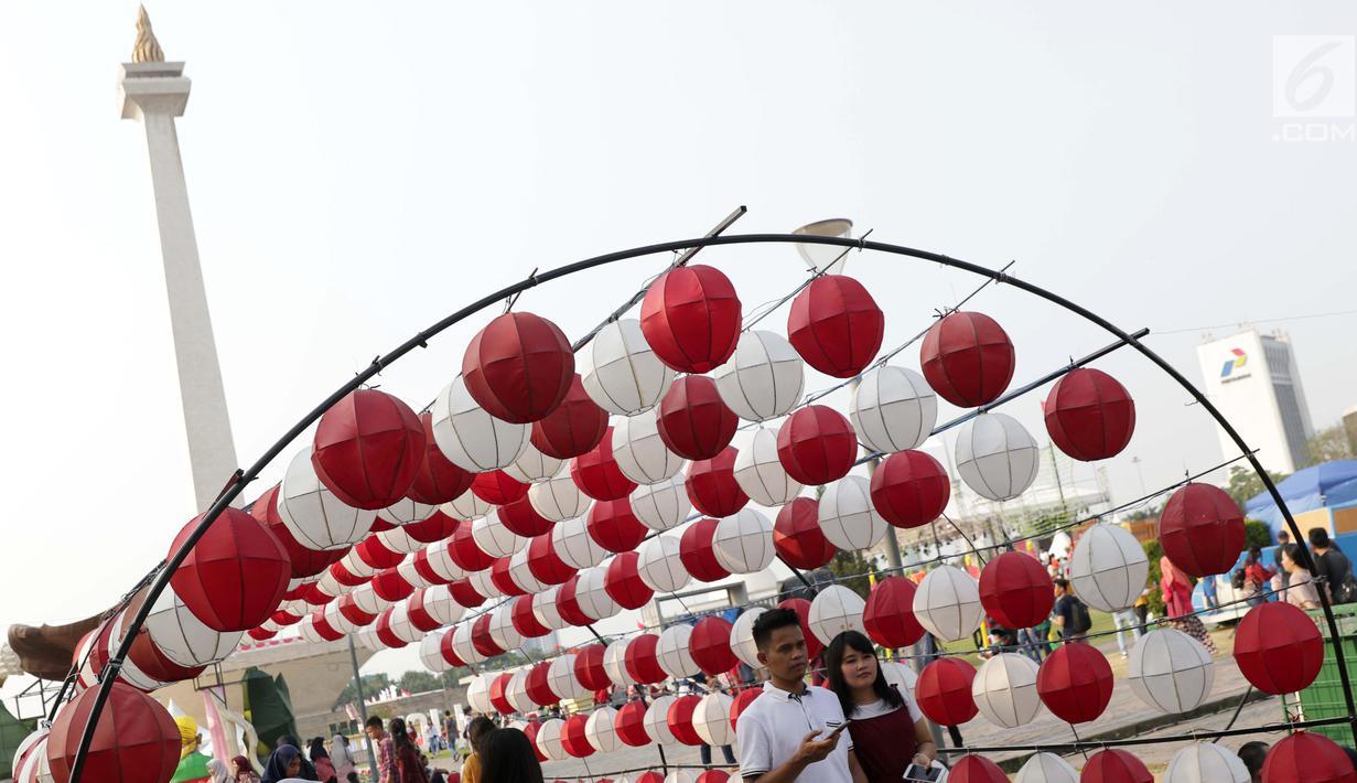 Pengunjung berjalan-jalan di area Monunen Nasional, Jakarta, Sabtu (17/8/2019). Libur perayaan HUT ke-74 Republik Indonesia yang bertepatan dengan akhir pekan dimanfaatkan warga untuk berjalan-jalan di kawasan Monas, Jakarta. (Liputan6.com/Helmi Fithriansyah)