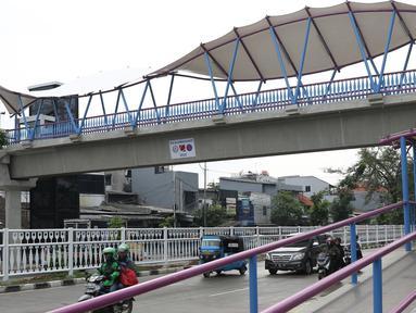 Pengendara melintas di bawah JPO Jelambar Barat di Jalan Pangeran Tubagus Angke, Jakarta, Sabtu (22/12). JPO Jelambar Barat memiliki atap berdesain modern dengan membran putih dengan model melengkung. (Liputan6.com/Helmi Fithriansyah)