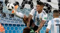 Pemain Argentina Marcos Rojo melompati pemain Nigeria Kelechi Iheanacho untuk merebut bola pada matchday terakhir Grup D Piala Dunia 2018 di Stadion St Petersburg, Selasa (26/6). Argentina meraih tiket ke 16 besar setelah menang 2-1. (AP/Petr David Josek)