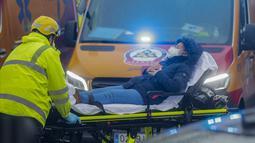 Petugas kesehatan mengevakuasi korban luka dari lokasi ledakan di pusat kota Madrid, Spanyol, Rabu (20/1/2021). Sedikitnya dua orang tewas dan delapan lainnya luka-luka setelah ledakan sangat keras tersebut. (AP Photo/Paul White)