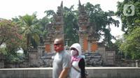 Wisatawan mengunjungi anjungan Provinsi Bali di Taman Mini Indonesia Indah (TMII), Jakarta, Minggu (21/6/2020). Setelah tidak beroperasi akibat pandemi, pengelola membuka kembali TMII dengan menerapkan protokol kesehatan pencegahan COVID-19 dan pembatasan pengunjung. (Liputan6.com/Immanuel Antonius)