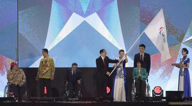Perwakilan dari China menerima bendera pada upacara penutupan Asian Para Games di Stadion Madya Senayan, Jakarta, Sabtu (13/10).(Bola.com/Vitalis Yogi Trisna)