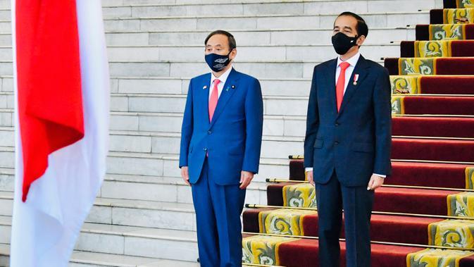 Presiden Joko Widodo bersama Perdana Menteri Jepang Yoshihide Suga (kiri), sama-sama mengenakan masker sebagai upaya mencegah penyebaran Covid-19, mendengarkan lagu kebangsaan saat upacara penyambutan di Istana Bogor, 20 Oktober 2020. (Laily Rachev/Indonesian Presidential Palace via AP)