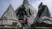 Relawan melepaskan penutup pelindung dari stupa candi Borobudur di Magelang, provinsi Jawa Tengah pada 17 Februari 2014 untuk memulai pembersihan endapan abu vulkanik menyusul letusan gunung berapi Gunung Kelud. (AFP Photo/Suryo Wibowo)