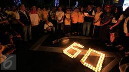 """Sejumlah karyawan Artha Graha mengikuti aksi """"Earth Hour"""" dengan menyalakan lilin membentuk angka 60 di kawasan SCBD Jakarta saat lampu-lampu di kawasan itu mulai dipadamkan selama satu jam pada Sabtu malam (19/3/2016). (Foto: Istimewa)"""
