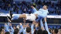 Para pemain Manchester City melemparkan rekan setimnya Sergio Aguero ke udara saat merayakan kemenangan gelar Liga Inggris setelah pertandingan melawan Everton di stadion Etihad di Manchester, Minggu (23/5/2021). (AP Photo / Dave Thompson, Pool)