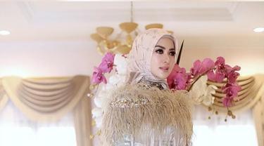 Syahrini berpose mengenakan gamis mewah berwarna krem dengan hiasan rumbai-rumbai di pundak. (Liputan6.com/Instagram/@princessyahrini)