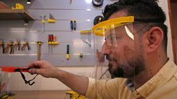 Seorang anggota staf merakit pelindung wajah cetak 3D yang dibuat di bawah proyek Glia, yang menghasilkan pasokan medis murah untuk daerah miskin, selama pandemi COVID-19 yang sedang berlangsung di Kota Gaza (13/7/2020). (AFP/Mohammed Abed)