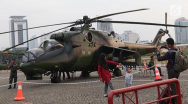 Warga berfoto berlatar helikopter TNI pada pameran Alat Utama Sistem Persenjataan TNI di Kawasan Monas, Jakarta, Kamis (27/9). Pameran ini bagian perayaan HUT TNI ke-73. (Liputan6.com/Helmi Fithriansyah)