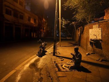 Seorang pria Muslim berdoa di jalan di luar Masjid Jama pada hari pertama Ramadan selama penguncian nasional untuk mengendalikan penyebaran virus corona Covid-19, di New Delhi, India (25/4/2020). (AP Photo/Manish Swarup)