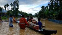 Tim Manggala Agni Daops Tinanggea yang menyalurkan bantuan bahan makanan dengan menggunakan perahu dan rakit darurat yang dibuat di wilayah pemukiman yang terendam banjir di Kabupaten Konawe. (Liputan6.com/Ahmad Akbar Fua)