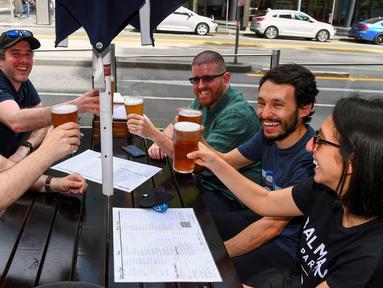 Pelanggan menikmati bir di sebuah pub di Melbourne, Australia, Jumat (22/10/2021). Kota terbesar kedua di Australia ini kembali dibuka setelah mengalami salah satu rangkaian lockdown pandemi yang paling lama di dunia. (William WEST/AFP)