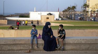 Sekeluarga memakai masker untuk mencegah penyebaran virus corona sambil menikmati malam mereka di tepi cornice, di Rabat, Maroko, Selasa (22/9/2020). (AP Photo / Mosa'ab Elshamy)
