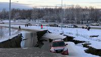 Satu mobil terperangkap di jalan Minnesota Drive yang amblas menyusul gempa bumi di Anchorage, Alaska, Jumat (30/11). Sebagian besar jalan layang di dekat bandara Anchorage runtuh, menjebak sebuah mobil di beton yang hancur. (AP Photo/Dan Joling)