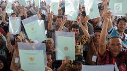 Warga menunjukkan sertifikat tanah saat mengikuti penyerahan sertifikat hak atas lahan tanah oleh Presiden Joko Widodo (Jokowi) di halaman depan Stadion Pakansari, Cibinong, Bogor, Selasa (25/9). (Merdeka.com/Arie Basuki)