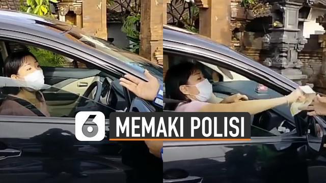 Seorang pengendara mobil memaki-maki anggota polisi ketika ditilang karena melanggar lampu merah.