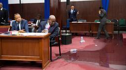 Anggota parlemen bekerja di tengah genangan air hujan yang membasahi lantai Gedung Parlemen Haiti, Port-au-Prince, Haiti, Rabu (21/8/2019). Kejadian itu terlihat ketika para anggota parlemen sedang memperdebatkan proses impeachment terhadap Presiden Haiti Jovenel Moise. (AP Photo/Dieu Nalio Chery)