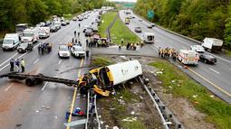 Personel darurat memeriksa kondisi bus sekolah yang bertabrakan dengan truk sampah di Interstate 80, Mount Olive, New Jersey, Kamis (17/5). Ada 45 orang berada di dalam bus, yakni tujuh orang dewasa dan 38 siswa. (Bob Karp/The Daily Record via AP)