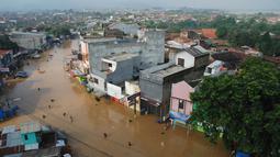Sejumlah warga melintasi genangan banjir untuk mengungsi di jalan Raya Dayeuhkolot, Kabupaten Bandung, Minggu (13/3). Kawasan Bandung Selatan kembali dilanda banjir akibat luapan Sungai Citarum dan membuat ribuan orang mengungsi. (Timur Matahari/AFP)