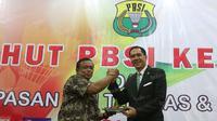 Ketua Umum PBSI, Gita Wirjawan (kanan), menyerahkan potongan tumpeng kepada mantan Ketua Umum PBSI, Djoko Santoso, dalam perayaan HUT PBSI ke-65 di Pelatnas Bulutangkis PBSI, Cipayung, Jakarta, (9/5/2016). (Bola.com/Arief Bagus)