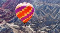Sebuah balon udara terbang di langit Taman Geologi Nasional Danxia di Zhangye, Provinsi Gansu, China barat laut, pada 26 Juli 2020. Sebuah festival balon udara internasional dibuka di Zhangye pada Minggu (26/7). Total 100 balon udara akan ditampilkan dalam festival tersebut. (Xinhua/Cheng Lin)