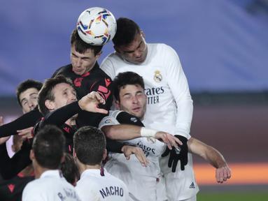 Para pemain Real Madrid dan Real Sociedad melompat untuk menyundul bola saat situasi tendangan sudut dalam laga lanjutan Liga Spanyol 2020/21 pekan ke-25 di Alfredo di Stefano Stadium, Madrid, Senin (1/3/2021). Real Madrid bermain imbang 1-1 dengan Real Sociedad. (AP/Bernat Armangue)