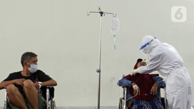 Petugas medis (kanan) yang mengenakan hazmat melakukan tes usap PCR di selasar IGD RSUD Cengkareng, Jakarta, Rabu (23/6/2021). Meningkatnya kasus COVID-19 di Ibu Kota Jakarta dalam beberapa hari terakhir mengakibatkan rumah sakit kewalahan. (Liputan6.com/Herman Zakharia)
