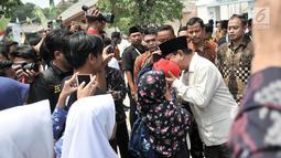 Calon presiden nomor urut 02 Prabowo Subianto mencium seorang anak saat menghadiri Rakernas LDII di Pondok Gede, Jakarta, Kamis (11/10). Prabowo datang dengan mengenekan kemeja safari cokelat dan peci hitam. (Merdeka.com/Iqbal Nugroho)