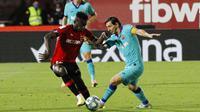 Striker Barcelona, Lionel Messi, berusaha melewati pemain Mallorca, Iddrisu Mohamed, pada laga La Liga di Estadio de Son Moix, Minggu (14/6/2020). Barcelona menang dengan skor 4-0. (AP/Francisco Ubilla)