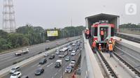 Pekerja menderek rangkaian kereta LRT Jabodebek yang baru tiba di Stasiun Harjamukti, Cibubur, Minggu (13/10/2019). Pengiriman prasarana gerbong LRT produksi PT INKA ke Jakarta dilakukan melalui jalur Tol Trans Jawa dan diangkut menggunakan multi-axle. (merdeka.com/Iqbal S Nugroho)