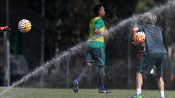 Semprotan air melintasi dekat asisten pelatih Miguel Gandia (kanan) saat memberikan instruksi pada sesi latihan Timnas U-22 Indonesia di Lapangan SPH, Karawaci, Jumat (17/3/2017).  (Bola.com/Nicklas Hanoatubun)