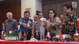 Menteri Keuangan Sri mulyani (kedua kiri) menunjukkan barang bukti hasil sitaan di Bea dan Cukai, Jakarta, Kamis (15/2). Sebanyak 142.519 botol minuman keras dan  12.919.499 batang rokok dimusnakan. (Liputan6.com/Anggan Yuniar)