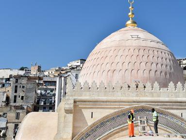 Pekerja sedang membersihkan bagian atap dekat kubah Masjid Ketchaoua atau Katsyawah di distrik Casbah, Aljir, Aljazair, Rabu (15/11). Masjid ini dibangun pada masa Dinasti Ottoman di abad ke-17. (AFP Photo/Ryad Kramdi)