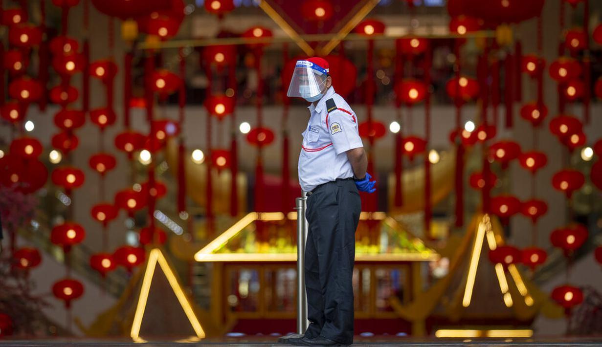 Seorang petugas keamanan mengenakan masker dan pelindung wajah saat berjaga di pintu masuk pusat perbelanjaan di Kuala Lumpur, Malaysia, Kamis (14/1/2021). Otoritas Malaysia memperketat pembatasan pergerakan untuk mencoba menghentikan penyebaran virus corona COVID-19. (AP Photo/Vincent Thian)