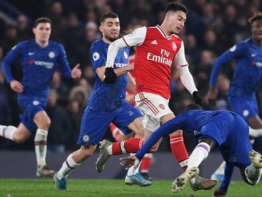 Striker Arsenal, Gabriel Martinelli, berebut bola dengan pemain Chelsea pada laga Premier League pekan ke-24 di Stamford Bridge, London, Rabu (22/1). Arsenal tahan imbang Chelsea 2-2. (AFP/Daniel Leal-Olivas)