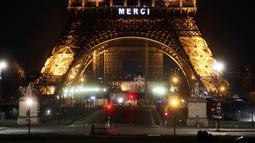 "Kata ""Merci atau terima kasih terpampang di Menara Eiffel, Paris, Jumat (27/3/2020). Menara Eiffel menyala untuk menampilkan pesan dukungan dan terima kasih kepada tenaga kesehatan di Prancis yang berada di garda depan memerangi pandemi COVID-19.  (AP/Thibault Camus)"