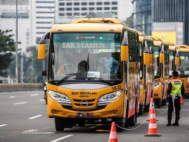 Bus sekolah terparkir di Kawasan Stasiun Sudirman, Jakarta, Jumat (19/6/2020). Dishub DKI Jakarta telah mengerahkan 50 armada bus sekolah untuk membantu mengurai lonjakan penumpang KRL yang ditempatkan di lima stasiun Tanah Abang, Manggarai, Juanda, Sudirman dan Tebet. (Liputan6.com/Faizal Fanani)