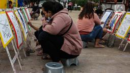 Aktivitas melukis di ruang kota Jalan Inpeksi Tanah Kusir, Jakarta, Senin (19/4/2021). Jalan Inpeksi Tanah Kusir ini menjadi salah satu tempat pilihan warga untuk menghabiskan waktu sembari menunggu berbuka puasa atau ngabuburit. (Liputan6.com/Johan Tallo)