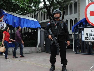 Petugas kepolisian berjaga di depan Gereja Katedral, Jakarta, Sabtu (24/12). Penjagaan dilakukan untuk menjaga kondusifitas agar acara Malam Misa Natal bisa berjalan lancar. (Liputan6.com/Helmi Afandi)