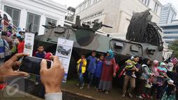 Warga berfoto disamping Panser Anoa dalam Habibie Festival di Museum Nasional, Jakarta, Minggu (14/8).Dalam Habibie Festival kali ini warga dapat melihat langsung Pesawat N250 dan Panser Anoa buatan anak bangsa tersebut. (Liputan6.com/Immanuel Antonius)