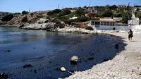 Turis berjalan di pinggir pantai yang tercemar tumpahan minyak di Pulau Salamina, Yunani, Selasa (12/9). Tumpahan bahan bakar itu kemudian meluas hingga 1,5 km dan kini mengotori pasir dan bebatuan karang sepanjang pesisir pantai. (AP/Petros Giannakouris)