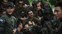 Marinir AS menonton marinir Korea Selatan mengeluarkan air dari pohon anggur selama latihan militer gabungan Cobra Gold antara militer AS dan Thailand di Chonburi, Thailand (19/2). (AFP Photo/Lilian Suwanrumpha)