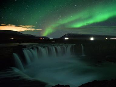 Langit berhias aurora borealis atau Cahaya Utara terlihat di atas air terjun Godafoss di Thingeyjarsveit, Islandia, 14 Oktober 2018. Lukisan abstrak alam semesta dari tabrakan spektrum warna Aurora Borealis begitu spektakuler. (Mariana SUAREZ/AFP)