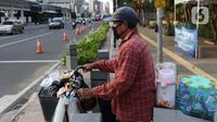Pedagang minuman keliling bersiap melintasi lajur penyebrangan di Jalan Jenderal Sudirman, Jakarta, Rabu (23//9/2020). Menkeu Sri Mulyani Indrawati memastikan ekonomi nasional resesi pada kuartal III-2020. Kondisi ini akan berdampak pada pelemahan daya beli. (Liputan6.com/Helmi Fithriansyah)