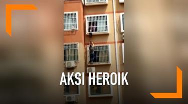 Aksi heroik dilakukan seorang pria di China, ia nekat bergelantungan di jendela apartemen demi selamatkan bocah yang hampir jatuh.