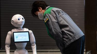 Gubernur Tokyo Yuriko Koike (kanan) melihat robot Pepper saat mengunjungi hotel yang diubah menjadi lokasi karantina pasien COVID-19 di Tokyo, Jepang, Jumat (1/5/2020). Sejumlah hotel di Tokyo mengerahkan robot untuk menyambut pasien COVID-19 dengan gejala ringan. (Philip FONG/AFP)