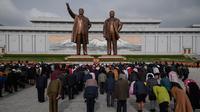 Orang-orang membungkuk ketika mereka memberi penghormatan kepada patung-patung pemimpin Korea Utara Kim Il Sung dan Kim Jong Il di Pyongyang (15/4). Mereka melakukan penghormatan untuk memperingati ulang tahun Kim Il Sung.  (AFP Photo/Ed Jones)