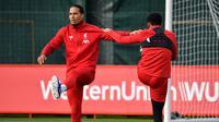 Bek Liverpool, Virgil van Dijk (kiri) melakukan pemanasan selama mengikuti sesi latihan tim di Melwood di Liverpool, Inggris barat laut (22/10/2019). Liverpool akan bertanding melawan wakil Belgia, Genk pada Grup E Liga Champions di Luminus Arena. (AFP/Paul Ellis)